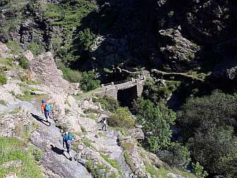Photo of scenery in Alpujarras with an old bridge and some people hiking on old paths